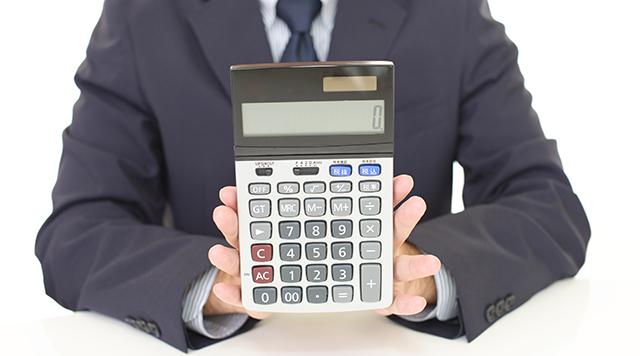 電卓で査定金額を示す人物